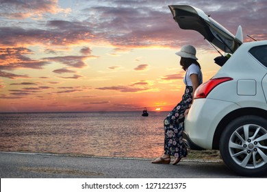 Side view of young woman traveler looking at beautiful sea sunset while sitting on hatchback car with the copy space, clouds and sky background