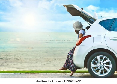 Side view of young woman traveler looking at beautiful cloudy blue sky over the sea while sitting on hatchback white car with copy space. Holiday and travel by car concept.