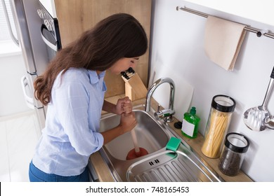 Side View Of A Young Woman Using Plunger In Blocked Kitchen Sink