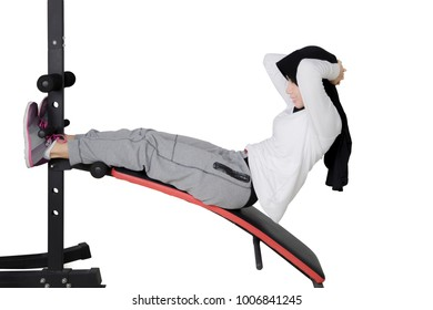 Side view of young woman wearing sportswear and veil while doing crunches, isolated on white background