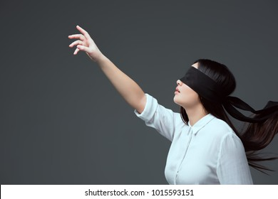 side view of young woman wearing black blindfold and raising hand isolated on grey