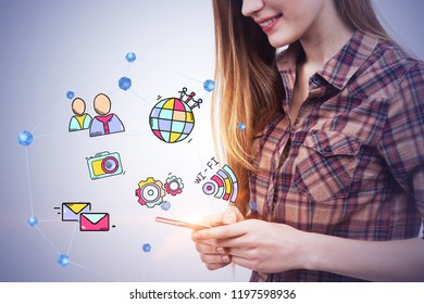 Side view of young woman wearing checkered shirt and smiling looking at her smartphone screen. Concrete wall background with colorful social media and internet icons. Toned image