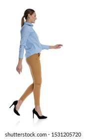 side view of young woman wearing blue shirt, smiling and walking isolated on white background