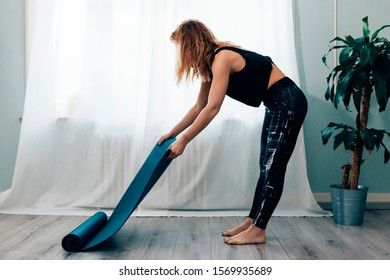 side view of a young woman in yoga outfit in front of a window unrolling the mat and starting doing exercises - fitness and healthy lifestyle and workout concept