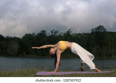 Side view of young women practicing yoga. asana Camatkarasana, Wild Thing