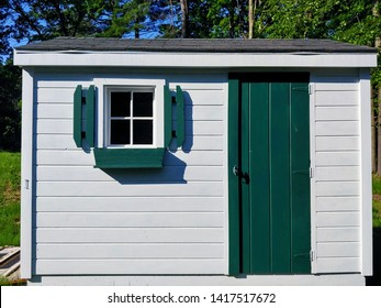side of a white and green shed with small windows and shudders