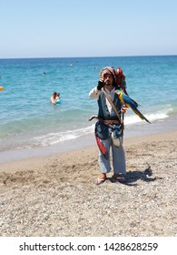 Side,Alany/Turkey-06.13.2019-A man dressed in a suit similar to Captain Sparrow urges tourists to take props: two parrots and a huge reptile.
