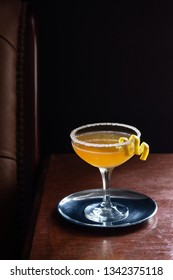 Sidecar Cocktail Served Straight Up with Sugared Rim in Dark Luxurious Bar or Restaurant