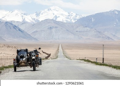 A sidecar motorcycle backed by a mountain range.