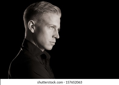 Side-face low key portrait of young handsome man in dark shirt looking up, black and white, isolated on black background.