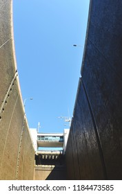 The sides of a lock on a river tower up towards a blue sky. The observation deck of the lock can be seen.