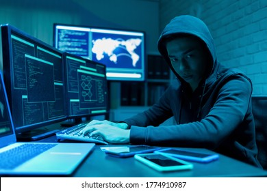 Sideview of asian male hacker use computer and smartphone to commit a crime
