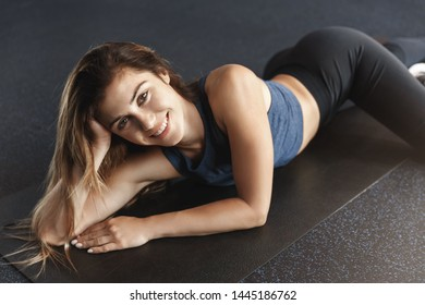 Side-view attractive feminine young sportswoman long hair wear yoga activewear, lying on rubber mat, cheerfully smiling, finish cardio exercise, leg-day gym training session, invite join workout