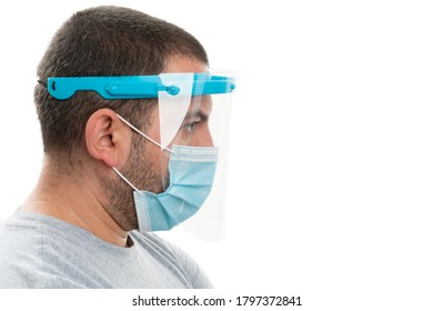 Side-view close-up of adult man wearing transparent face shield and medical or surgical disposable protection mask as virus covid19 sars flu infection pandemic prevention with blank copyspace