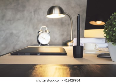 Sideview of desktop with graphic tablet, plant, alarm clock, illuminated lamp and computer. Concrete wall background
