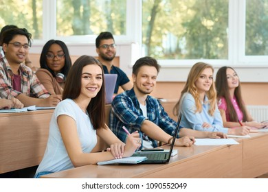 Sideview of groupmates looking at camera during the lesson. Studying on wooden desks. Guys reading, studuing, learning, writing. Working with scientific project. Feeling happy, satisfied.