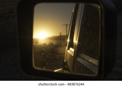 Sideview mirror reflection of dusty road