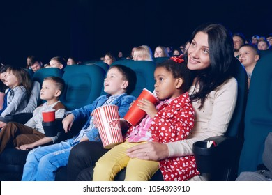Sideview of nice mother and daughter watching interesting movie in cinema hall on other people's background. Little girl wearing colorful clothes, drinking cola and eating popcorn.