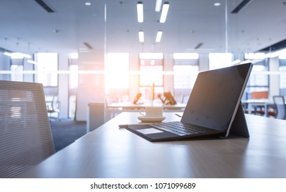 Sideview of office desktop with blank laptop and various blurry background