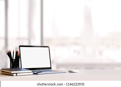Sideview of office desktop with blank laptop and various office tools on wood desk.