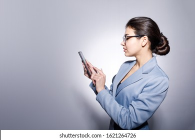 Sideview Portrait of Attractive Young Businesswoman Using Smartphone