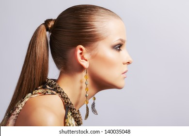 sideview portrait of beautiful young long-haired brunette woman in ear-rings on gray