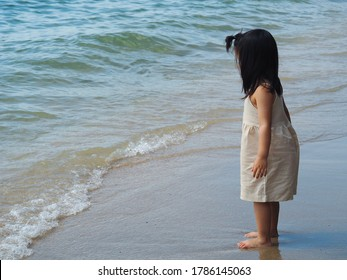 Sideview portrait of happy young toddler girl in light brown overalls barefoot standing at the sandy beach. The kid hesitate to get into the water. Kid outdoor activities concept.