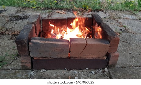 Sideview of rustic mangal built from cracked burnt terracotta bricks with smoky surface. Flaming fire inside rough brazier. Grunge outdoor scene. Bonfire flames. Camping concept. Outdoor mangal