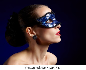 sideview shoulder portrait of beautiful brunette woman in carnival mask