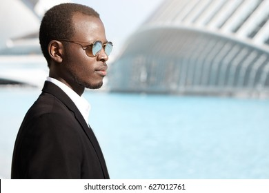 Sideview of smiling stylish dark-skinned banker wearing black suit and round sunglasses walking to office in urban surroundings, having confident and determined look, thinking about upcoming meeting