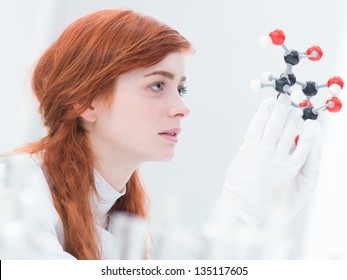 side-view of a student analyzing a  citric acid molecular model  in a chemistry lab