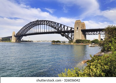side-view of Sydney Harbour bridge from milsons point on bright summer sunny day with green trees surrounding harbour water