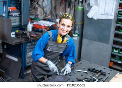Sideview of worker woman marking piece of metal being absorbed in her work