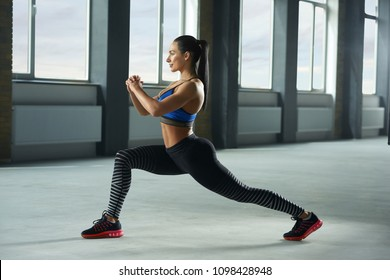 Sideview of young sporty girl with athletic body doing fallouts in gym. Having sturdy muscles, healthy body and tanned skin. Looking strong, fit, feeling good. Wearing comfortable stylish sportswear.