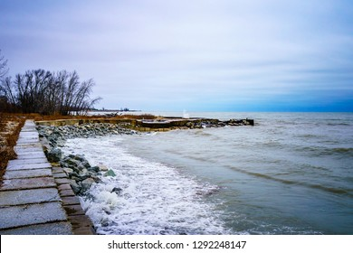 A sidewalk along the Lake Michigan shore leading to a pier at the end of the path, shot on a windy, cold and cloudy afternoon.