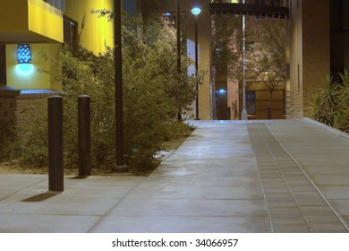 A sidewalk between buildings well lit up at night time.