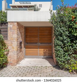 sidewalk by upscale house entrance solid wooden door and foliage
