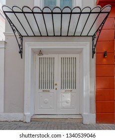 sidewalk by white vintage house door with glass and metal cover