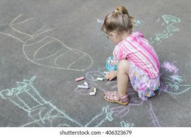 Sidewalk chalk drawings of little Caucasian girl wearing pink ruffle skirt