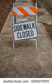 Sidewalk Closed Sign Askew with Copy Space Below over sidewalk