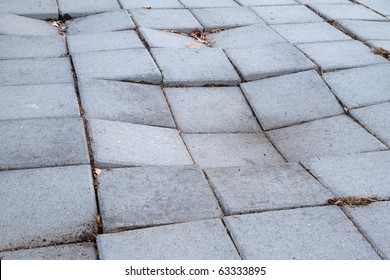 Sidewalk of concrete tiles that are starting to sink and have created a depression