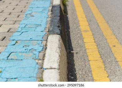 Sidewalk curb and street with different colored painted lines.