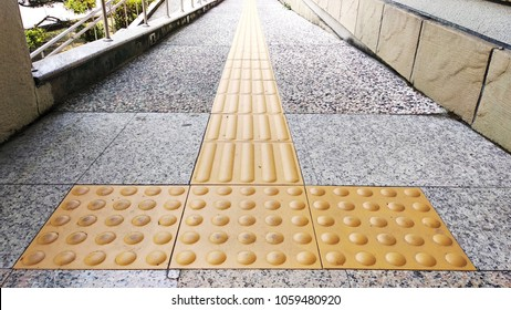 Sidewalk guides for blind.Yellow tactile tile for people with poor eyesight