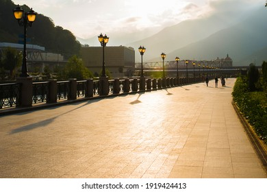 the sidewalk illuminated by the sun, along the sidewalk there are lanterns, people walking on the sidewalk against the backdrop of mountains and sunset - Shutterstock ID 1919424413