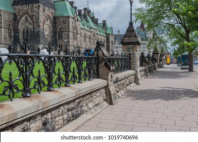 Sidewalk in Ottawa, Ontario Canada with black wrought iron fence above a stone wall barrier on the side