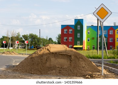 sidewalk repair along the highway. a pile of sand for the substrate for paving slabs. The colorful house in the background is a kindergarten