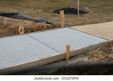 sidewalk repaired with newly poured cement wooden work - Shutterstock ID 1912373995