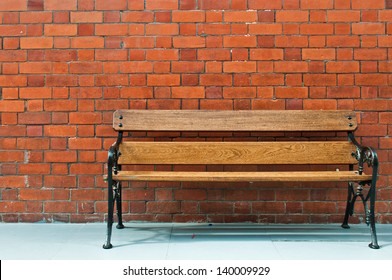 sidewalk scene with wooden bench and brick wall
