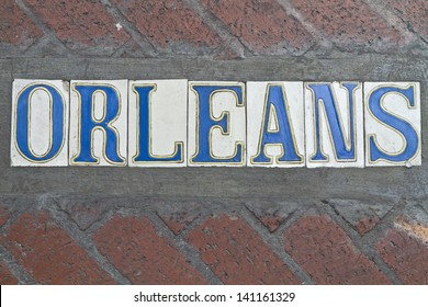 SIdewalk street sign for Rue Orleans in the French Quarter of New Orleans, Louisiana