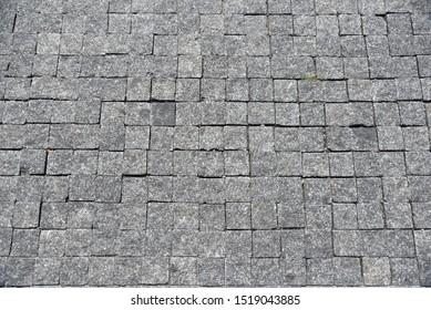 Fußgängeroberfläche gepflastert mit schwarzen Straßenfliesen. Draufsicht.